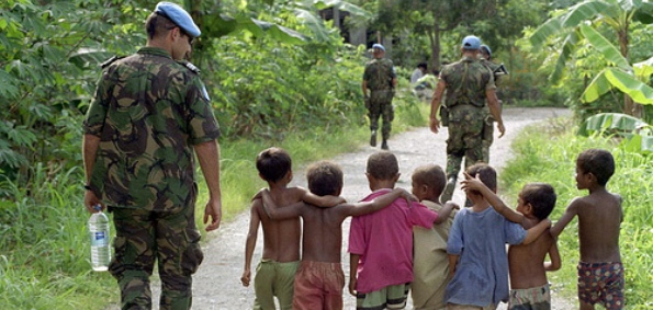 DILI, TIMOR-LESTE - Members of the United Nations Transitional Administration in East Timor (UNTAET) Portuguese contingent are accompanied by a group of local children as they conduct a security patrol. (UN Photo/Eskinder Debebe)