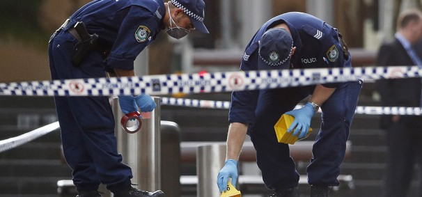 Police officers place marker cones over potential evidence in their investigation into the Sydney cafe siege